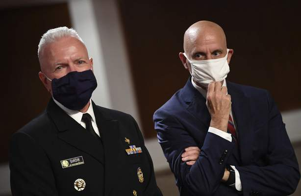 Adm. Brett Giroir, left, director of the U.S. coronavirus diagnostic testing, and Food and Drug Administration (FDA) Commissioner Stephen Hahn, prepare to testify before a Senate Health, Education, Labor and Pensions Committee hearing on Capitol Hill in Washington, Tuesday, June 30, 2020. (Kevin Dietsch/Pool via AP)
