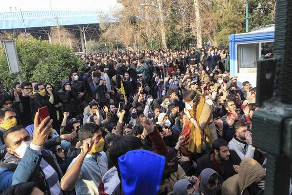 FILE - In this Dec. 30, 2017 file photo taken by an individual not employed by the Associated Press and obtained by the AP outside Iran, university students attend a protest inside Tehran University while anti-riot Iranian police prevent them to join other protestors, in Tehran, Iran. (AP Photo, File)