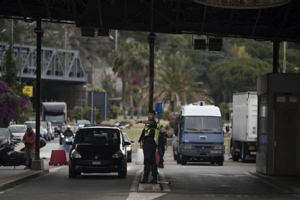 FILE - In this Monday, June 15, 2020 file photo, a French gendarme gestures to a pedestrian at the Saint-Ludovic border check point on the Franco-Italian border in Menton, France. (AP Photo/Daniel Cole, File)