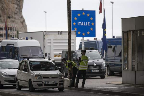 FILE - In this Monday, June 15, 2020 file photo, French gendarmes approach a car at the Saint-Ludovic border check point on the Franco-Italian border in Menton, France. (AP Photo/Daniel Cole, File)