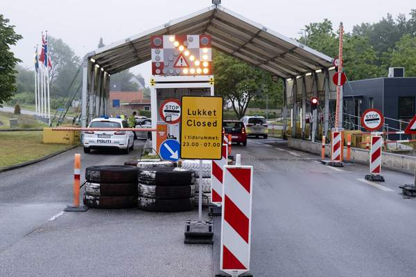 FILE - In this Saturday, June 13, 2020 file photo, a sign with the opening hours of the border checkpoint between Harrislee in Germany and Padborg in Denmark is displayed in front the border crossing in Harrislee, Germany. (Frank Molter/dpa via AP, File)