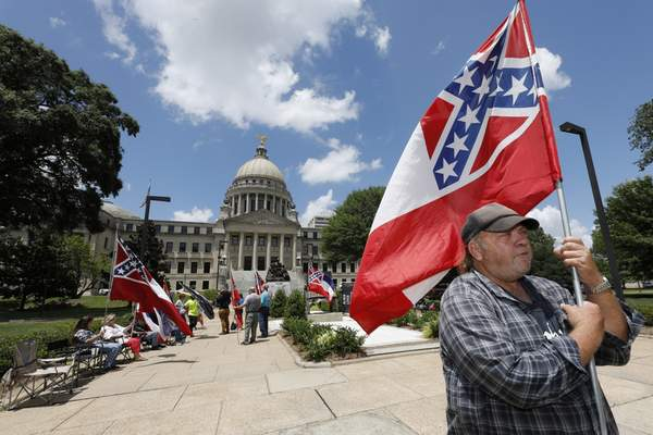 FILE - In this Sunday, June 28, 2020, file photo, David Flynt of Hattiesburg, stands outside the state Capitol with other current Mississippi flag supporters in Jackson, Miss. (AP Photo/Rogelio V. Solis, File)