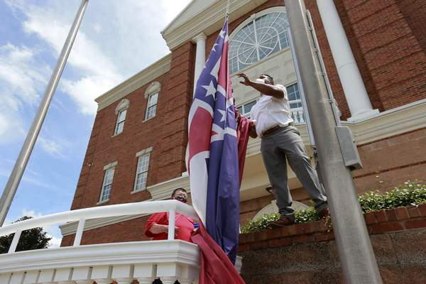 FILE - In this Monday, June 29, 2020, file photo, City of Tupelo Community Outreach Coordinator Marcus Gary takes down the Mississippi state flag that flew over the City Hall of Tupelo one last time Monday, June 29, 2020. (Thomas Wells/The Northeast Mississippi Daily Journal via AP, File)
