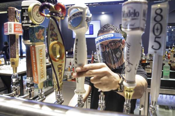 Associated Press A bartender pours a beer while wearing a mask and face shield  at Slater's 50/50 on Wednesday in Santa Clarita, Calif.