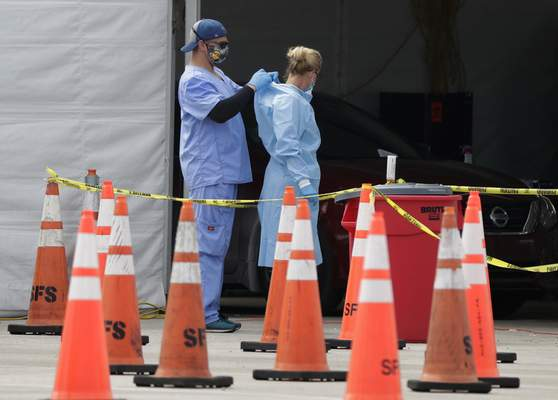 Associated Press  Health care workers help each other with their personal protective equipment at a drive-thru coronavirus testing site outside Hard Rock Stadium in Miami Gardens, Fla.