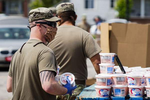 FILEMembers of the Indiana National Guard's 1st Battalion, 293rd Infantry Regiment load food into vehicles during the Community Harvest Farm Wagon distribution at Parkview Field in April.