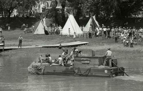 July 12, 1969: A converted barge filled with full-blooded Sioux and Dakota Indians passes a replica Indian Village during the river parade at the first Three Rivers Festival. More than 10,000 lined the banks of the St. Joseph to watch the parade. (Journal Gazette file photo)
