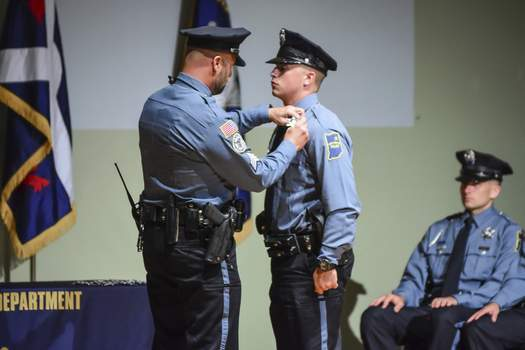 Photos by Mike Moore | The Journal Gazette Fort Wayne Police Academy graduate Brock Ingram, right, is pinned Friday by his father, Sgt. Daniel Ingram, at a ceremony at the Public Safety Academy. (The_Journal_Gazette)