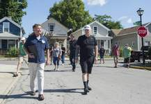 Michelle Davies | The Journal Gazette  City Councilman Geoff Paddock, left, walks with Bloomingdale neighborhood president Bob Shoemaker, as they talk about concerns during a walk Saturday morning with other residents.