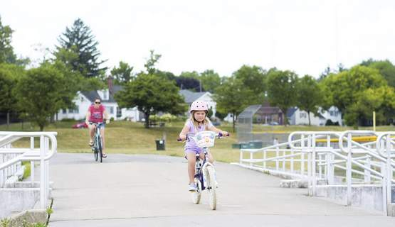 Katie Fyfe | The Journal Gazette Celeste Bauer, 5, goes for a bike ride with her mother Sara Bentley through Hamilton Park on Tuesday, July 7th, 2020.