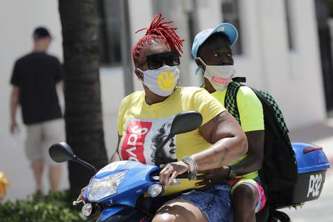 Virus Outbreak Florida Associated Press People wearing masks ride a scooter in Miami Beach, Fla.,on Sunday as virus cases soared across the state. (Lynne SladkySTF)