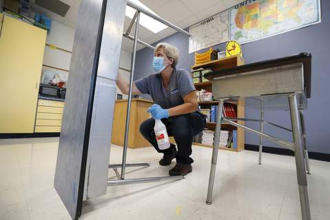 Virus Outbreak Associated Press Des Moines Public Schools custodian Cynthia Adams cleans a desk in a classroom at an elementary School in Des Moines, Iowa, on Wednesday. (Charlie NeibergallSTF)