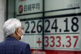 Japan Financial Markets Associated Press A man wearing a face mask to help curb the spread of the coronavirus looks at an electronic stock board Monday showing Japan's Nikkei 225 index at a securities firm in Tokyo. (Eugene HoshikoSTF)