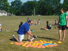 Victoria Jacobsen | The Journal Gazette Blackhawk Christian girls soccer coach Tim Kintz sanitizes practice cones while his players stretch after practice Tuesday in an effort to keep the players safe as sports teams start back up.