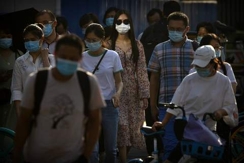 APTOPIX Virus Outbreak China People wearing face masks to protect against the coronavirus wait to cross an intersection in the central business district in Beijing, Wednesday, July 15, 2020. (AP Photo/Mark Schiefelbein) (Mark Schiefelbein STF)