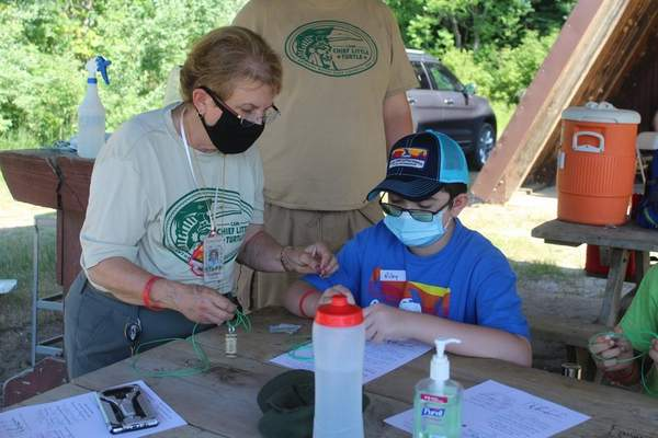 CourtesyMandie Walker Volunteer Penny Myers of Wolcottville, a registered fishing merit badge councilor, works with a Boy Scout atCamp Chief Little Turtle in Pleasant Lake while wearing face masks amid the coronavirus pandemic.