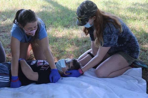 CourtesyMandie Walker Amelia Walker, left, of Troop 597 Girls in Auburn, and Mary Yankowiak of Venture Crew 2802 of Fort Wayne practice first aid with Alex King from Troop 125 in Angola atCamp Chief Little Turtle.