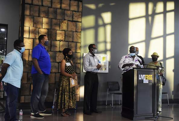 Katie Fyfe | The Journal Gazette  Pastor Anthony Payton speaks at the end of the event about everything that occurred at the Promenade Park Foundation Pavilion on Thursday.