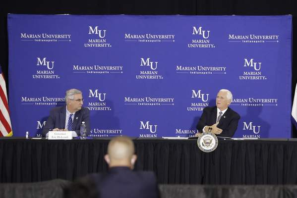 Vice President Mike Pence, right, speaks as Indiana Gov. Eric Holcomb listens during a meeting with higher education leaders on safely reopening schools, Friday, July 24, 2020, in Indianapolis. (AP Photo/Darron Cummings)