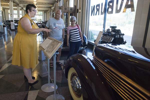 Michelle Davies   The Journal Gazette Elyse Faulkner, education and programs manager at the Auburn Cord Duesenberg Automobile Museum, talks with visitors Marie and Robert Clark, of Toledo, about the unique features of the 1936 Cord 810.