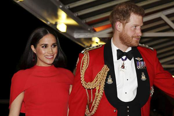 """FILE - In this Saturday March 7, 2020 file photo, Britain's Prince Harry and Meghan, Duchess of Sussex arrive at the Royal Albert Hall in London, , to attend the Mountbatten Festival of Music. Prince William infuriated Prince Harry when he told his younger brother he should move slowly in his relationship with the former Meghan Markle, fearing that he was being """"blindsided by lust,'' a new book on the Windsors says. The second installment of a serialized version of the book """"Finding Freedom,"""" which appeared in the Sunday Times, Sunday, July 26, 2020 claimed that Harry was angered by what he perceived to be as William's snobby tone in a discussion about the American actress. (Simon Dawson/Pool via AP, file)"""