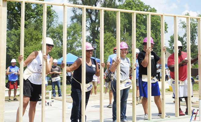 Katie Fyfe   The Journal Gazette  Youth for Christ's City Life ministry teams up volunteers fromFort Wayne Unitedandthe Fort Wayne Police Department to build the first walls for a Habitat for Humanity of Greater Fort Waynehomeon Gay Street on Sunday.