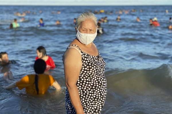 A woman wearing a face mask stands on a beach in Vung Tau city, Vietnam, Sunday, July 26, 2020. (AP Photo/Hau Dinh)