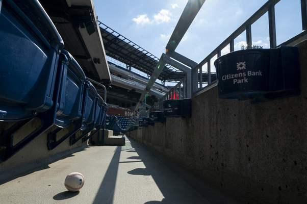 A foul ball that was hit into the stands sits on the floor of an empty stadium during the eighth inning of a baseball game between the Miami Marlins and the Philadelphia Phillies, Sunday, July 26, 2020, in Philadelphia. (AP Photo/Chris Szagola)