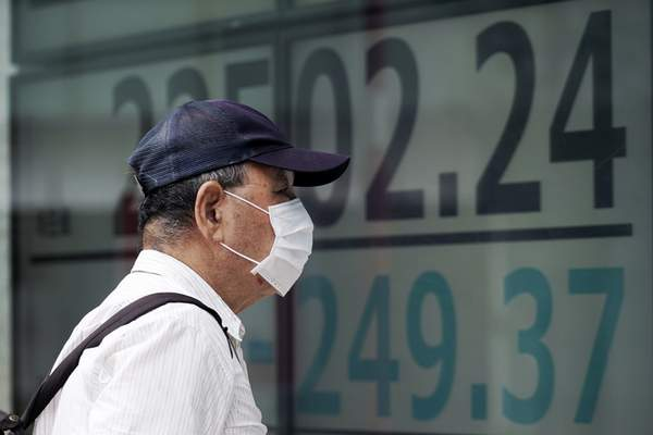 A man looks at an electronic stock board showing Japan's Nikkei 225 index at a securities firm in Tokyo Monday, July 27, 2020. (AP Photo/Eugene Hoshiko)
