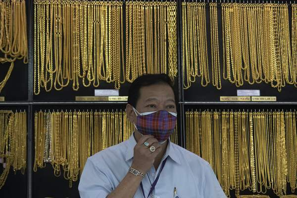 FILE - In this April 16, 2020, file photo, a Thai shopkeeper adjusts his face mask at a gold shop in Bangkok, Thailand. (AP Photo/Sakchai Lalit, File)