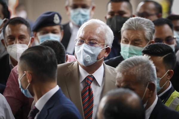 Former Malaysian Prime Minister Najib Razak, center, wearing a face mask with his supporters arrives at courthouse in Kuala Lumpur, Malaysia, Tuesday, July 28, 2020. (AP Photo/Vincent Thian)