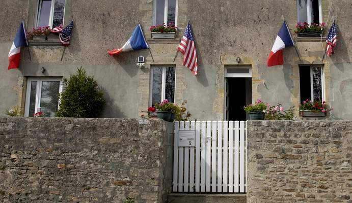 French and U.S. flags decorate a house front near Omaha Beach, Thursday, June 4, 2020, in Saint-Laurent-sur-Mer, Normandy, France. (AP Photo/Virginia Mayo, File)