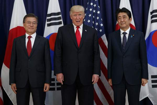 U.S. President Donald Trump meets with Japan's Prime Minister Shinzo Abe, right, and South Korea's President Moon Jae-in before the Northeast Asia Security dinner at the US Consulate General Hamburg, in Hamburg, Germany, July 6, 2017. (AP Photo/Evan Vucci, File)