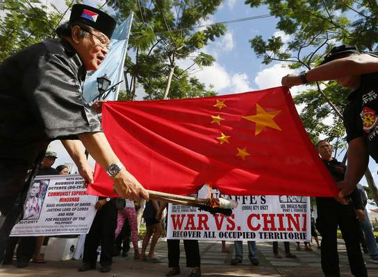 Philippine presidential candidate Elly Pamatong burns a Chinese flag in Manila, Dec. 4, 2015, to denounce China's island-building at the disputed Spratly Islands in the South China Sea. (AP Photo/Bullit Marquez, File)
