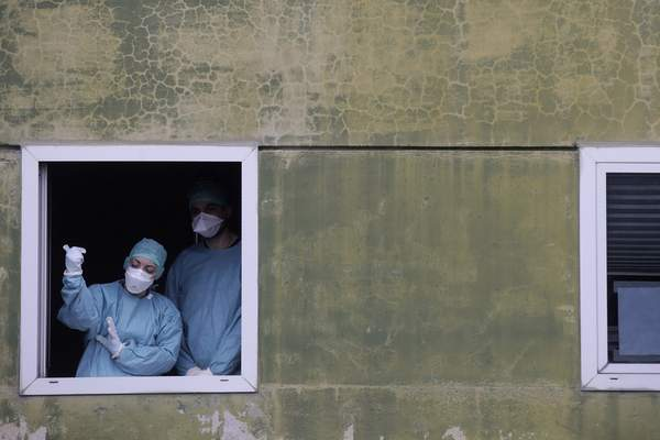 FILE - In this Thursday, March 12, 2020 file photo, medical staff in work at one of the emergency structures that were set up to ease procedures at the Brescia hospital, northern Italy.  (AP Photo/Luca Bruno)
