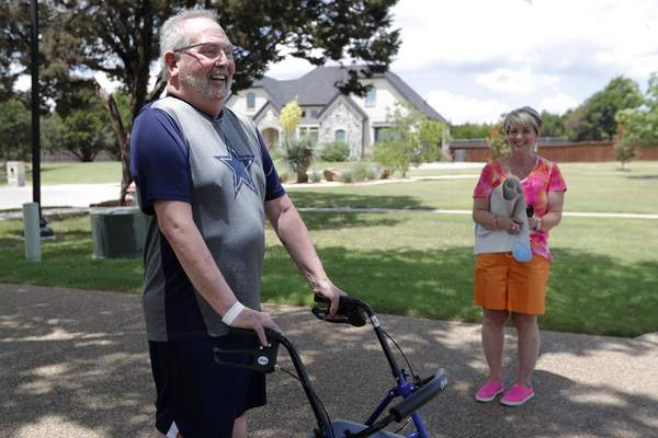 Stephen Donelson, left, smiles as he walks up his driveway to his home accompanied by his wife, Terri, in Midlothian, Texas on Friday, June 19, 2020, after his 90-day stay in the Zale Hospital on the UT Southwestern Campus. (AP Photo/Tony Gutierrez)