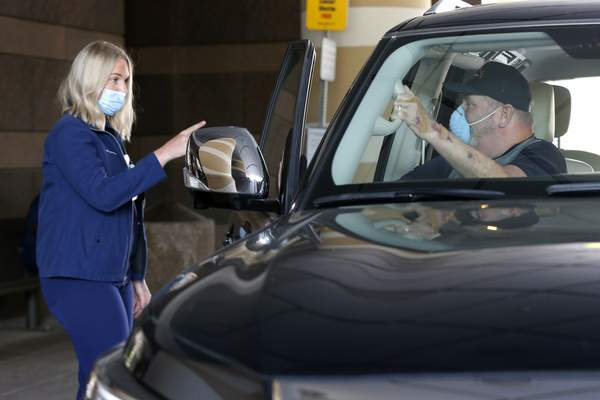Molly Gough, a speech therapist at the Zale Hospital on the UT Southwestern Campus speaks with patient Stephen Donelson as he departs the hospital in Dallas, Friday, June 19, 2020. (AP Photo/Tony Gutierrez)