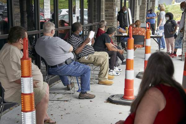 FILE - In this July 15, 2020, file photo, job seekers exercise social distancing as they wait to be called into the Heartland Workforce Solutions office in Omaha, Neb. (AP Photo/Nati Harnik, File)