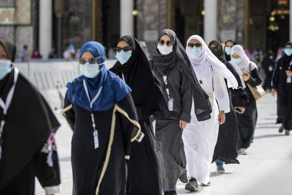 In this photo released by the Saudi Media Ministry, a limited numbers of pilgrims move several feet apart, circling the cube-shaped Kaaba in the first rituals of the hajj, as they keep social distancing to limit exposure and the potential transmission of the coronavirus, at the Grand Mosque in the Muslim holy city of Mecca, Saudi Arabia, Wednesday, July 29, 2020. (Saudi Media Ministry via AP)
