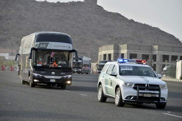 A police vehicle escorts a pilgrim convoy as they move towards the Grand Mosque ahead of the Hajj pilgrimage in the Muslim holy city of Mecca, Saudi Arabia, Wednesday, July 29, 2020. (AP Photo)