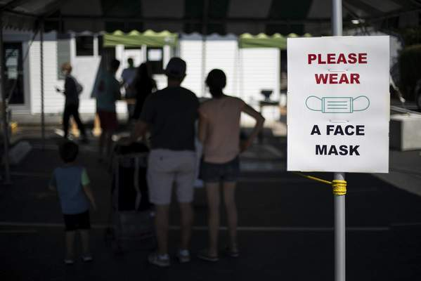 Associated Press Customers with masks line up at a Brickley's Ice Cream in Narragansett, R.I., on Wednesday.As COVID-19 cases continue to rise, so to do conspiracy theories about the virus.