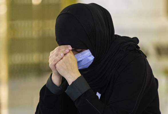 In this photo released by the Saudi Media Ministry, a woman, among a limited numbers of pilgrims, prays in the first rituals of the hajj, while keeping social distancing to limit exposure and the potential transmission of the coronavirus, at the Grand Mosque in the Muslim holy city of Mecca, Saudi Arabia, Wednesday, July 29, 2020. (Saudi Media Ministry via AP)