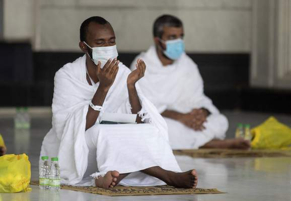 In this photo released by the Saudi Media Ministry, a limited numbers of pilgrims pray in the first rituals of the hajj, as they keep social distancing to limit exposure and the potential transmission of the coronavirus, at the Grand Mosque in the Muslim holy city of Mecca, Saudi Arabia, Wednesday, July 29, 2020. (Saudi Media Ministry via AP)