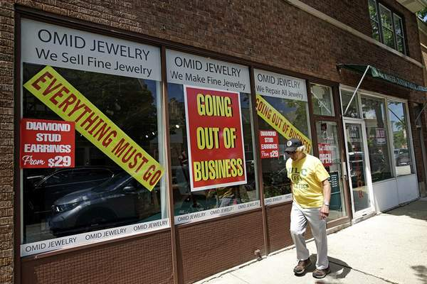 FILE - A man walks past a retail store that is going out of business due to the coronavirus pandemic in Winnetka, Ill., Tuesday, June 23, 2020. (AP Photo/Nam Y. Huh)