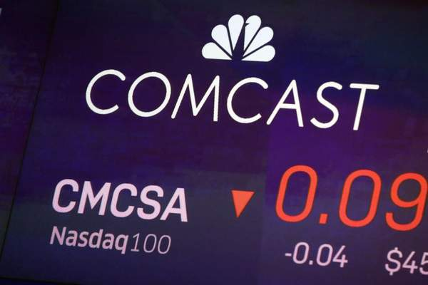 In this Oct. 1, 2019, file photo the symbol for Comcast appears on a screen at the Nasdaq MarketSite, in New York. (AP Photo/Richard Drew, File)