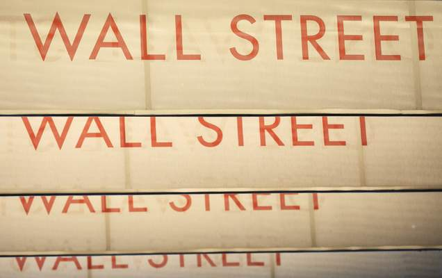 Signs for Wall Street are shown, Thursday, July 30, 2020, in New York. Stocks are falling on Wall Street Thursday after reports showed that layoffs are continuing at a stubborn pace and that the U.S. economy contracted at a nearly 33% annual rate in the spring. (AP Photo/Mark Lennihan)