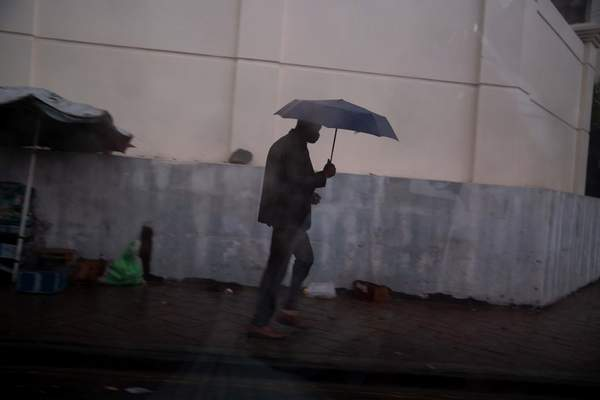 A man walks in the rain brought by the outer bands of Hurricane Isaias in the Petionville district of Port-au-Prince, Haiti, Friday, July 31, 2020. Isaias kept on a path early Friday toward the U.S. East Coast as it approached the Bahamas. (AP Photo/Dieu Nalio Chery)
