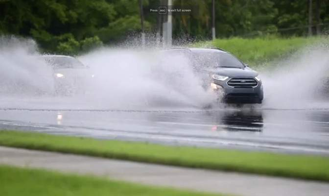 In this image made from video, cars drive through high water on a road in Canovanas, Puerto Rico, Thursday, July 30, 2020. Tropical Storm Isaias knocked out power and caused flooding and small landslides across Puerto Rico and the Dominican Republic on Thursday as forecasters predicted it would strengthen into a hurricane while moving toward the Bahamas and U.S. East Coast.(AP Photo)