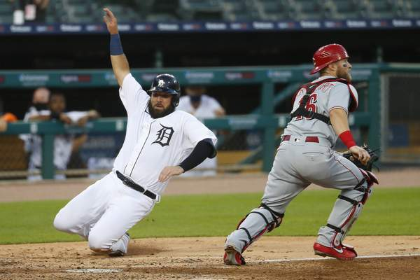 Associated Press Detroit's Austin Romine slides safely into home as Reds catcher Tucker Barnhart waits for the throw Friday in Detroit.