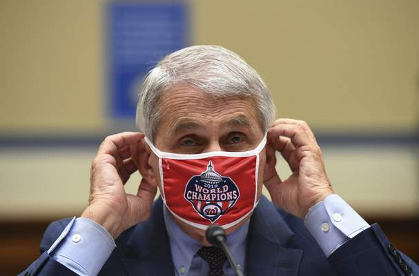Associated Press Dr. Anthony Fauci adjusts his face mask Friday during a House subcommittee hearing on the coronavirus.